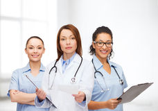 Calm female doctor with clipboard. Healthcare and medicine concept - calm female doctor and nurses with clipboard and stethoscope giving prescription Stock Photo