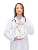 Calm female doctor with wall clock. Healthcare and medicine concept - calm female doctor with wall clock and stethoscope Royalty Free Stock Photography