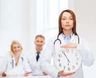 Calm female doctor with wall clock. Healthcare and medicine concept - calm female doctor with wall clock and stethoscope Royalty Free Stock Images