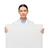 Calm female doctor with white blank board. Healthcare, advertisement and medicine concept - calm female doctor with white blank board Royalty Free Stock Image