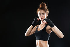 Calm female fighter ready to fight. While looking at the camera over black background Stock Image