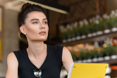 Calm female freelancer in a public space. Thoughtful look of a stylish woman with a copy space Stock Image