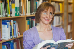 Calm female librarian posing holding an opened book Royalty Free Stock Image