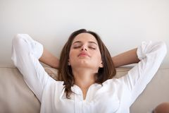 Calm female lying hands over head relaxing at home Stock Photography