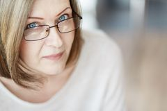 Calm female. Mature woman in eyeglasses looking at camera Stock Photo