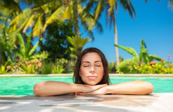 Calm female in the pool. Closeup portrait of a beautiful calm female with closed eyes enjoying bright warm sun light, relaxation in a swimming pool, luxury Royalty Free Stock Photography