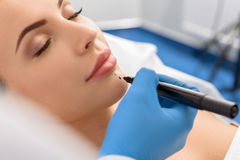 Calm female is ready for decorative surgery. Focus on close up face of serene woman preparing for plastic operation on face Stock Photo