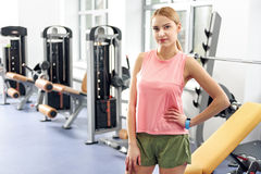 Calm female situating in gym. First day in fitness center. Portrait of serene woman standing in wide room with different types of equipment in it. Sport concept Royalty Free Stock Images
