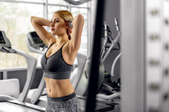 Calm female training in fitness center. Side view girl expressing seriousness while doing exercise in workout room Royalty Free Stock Photography