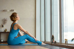 Calm female yogi relaxing in apartment. Peaceful young girl is enjoying yoga in the morning. She is sitting on mat near window and bending leg to abdomen. Her Stock Images