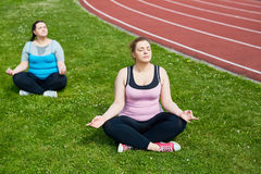 Yoga for relax. Calm females in activewear sitting in pose of lotus on green lawn Royalty Free Stock Photos