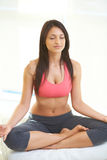 Calm fitness woman while sitting in yoga lotus pose Stock Photos