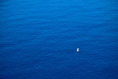 Calm flat surface of ocean and small fisher boat. Mediterranean Sea. Near Greece islands royalty free stock photos