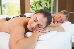 Calm friends lying on massage tables with hot stones on their backs Stock Images
