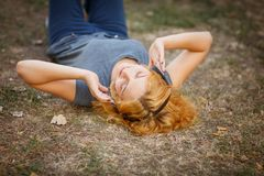 Calm ginger girl in headphones relaxing on a grass background. Free time concept. stock photos