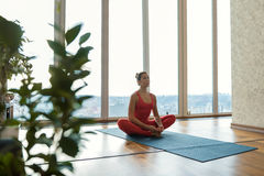 Calm girl doing mediation in apartment. Peace and pleasure. Tranquil young woman is sitting in lotus position and meditating. Big window with city view on Stock Photos