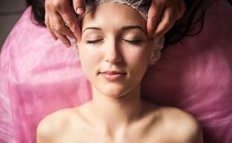 Calm girl having spa facial massage in luxurious beauty salon Royalty Free Stock Photography