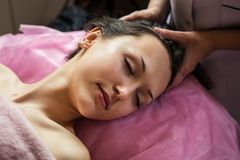 Calm girl having spa facial massage in luxurious beauty salon Stock Images