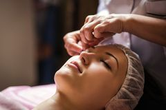 Calm girl having spa facial massage in luxurious beauty salon Royalty Free Stock Photo