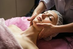 Calm girl having spa facial massage in luxurious beauty salon Stock Image