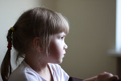 Calm girl-preschooler profile indoors Royalty Free Stock Photography