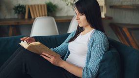 Calm girl is reading book sitting on couch at home turning pages enjoying peace, literature and comfort. Nice loft style. Living room is visible in background stock video footage