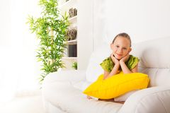 Calm girl sitting on coach with pillow Royalty Free Stock Photography