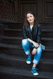 A calm girl in sneakers, jeans and a leather jacket sits on wood Stock Photography