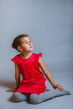 Calm girl teenager sits in a red dress looking to Royalty Free Stock Photos