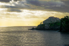 Calm golden sea with hotel on cliffs. Calm golden and blue coloured sea with big hotel on cliffs in the background. Afternoon sun with dark clouds and bright royalty free stock photos