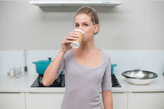 Calm gorgeous blonde drinking from disposable cup Royalty Free Stock Photos