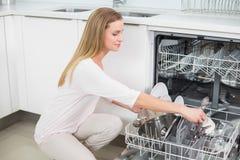Calm gorgeous model kneeling next to dish washer Stock Photo