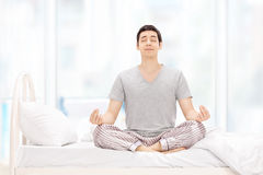 Calm guy meditating seated on bed Royalty Free Stock Image