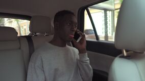 Calm handsome african man in casual clothes talking on cellphone while riding in backseat of taxi cab. Cheerful black