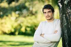 Calm handsome man leaning on tree stem Stock Photo