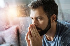 Calm handsome man looking aside and thinking. Full concentration. Calm handsome unshaken man looking aside thinking and holding hands near mouth Stock Photos