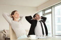 Calm happy businessman and businesswoman relaxing in ergonomic o. Calm happy businessman and businesswoman relaxing with eyes closed, hands behind head sitting Stock Photography