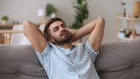 Calm happy young man relaxing having nap on comfortable couch. Calm happy young man relaxing with eyes closed or having healthy nap on comfortable couch stock video