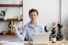 Calm healthy business woman meditate relaxing at office desk stock image