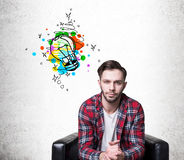 Calm hipster guy with an idea in armchair. Portrait of a calm hipster guy sitting in a leather armchair near a concrete wall with a colorful light bulb to the Royalty Free Stock Image