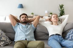 Calm husband and wife relax on couch hands over head. Calm husband and wife lying on cozy couch hands over head, peaceful millennial couple stretch relaxing on royalty free stock photo