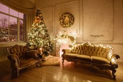 Calm image of interior Classic New Year Tree decorated in a room with fireplace Stock Images