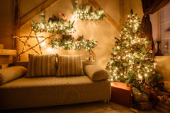 Calm image of interior modern home living room decorated christmas tree and gifts, sofa, table covered with blanket. Royalty Free Stock Image