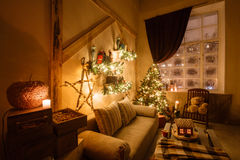 Calm image of interior modern home living room decorated christmas tree and gifts, sofa, table covered with blanket. Stock Photos