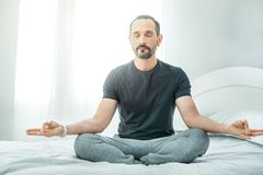 Handsome unshaken man sitting and meditating. Calm inside. Handsome unshaken pleasant man sitting on the bed taking right position and meditating Royalty Free Stock Photography