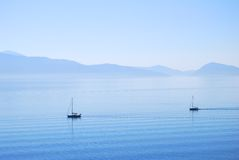 Calm ionian sea waters with sailing yachts. And land in the distance Stock Image