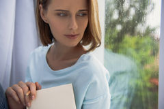 Calm lady enjoying raining day. Cute lady with book looking at rain, fall blues concept Royalty Free Stock Image