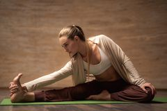 Calm lady leaning to the foot while stretching on yoga mat royalty free stock image