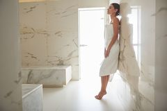 Calm lady standing on her toes and leaning towards the wall royalty free stock photography