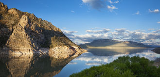 Calm lake in the American West reflecting a rocky point. Calm water of the Buffalo Bill Reservoir in Wyoming reflecting a rocky point in morning light Royalty Free Stock Images